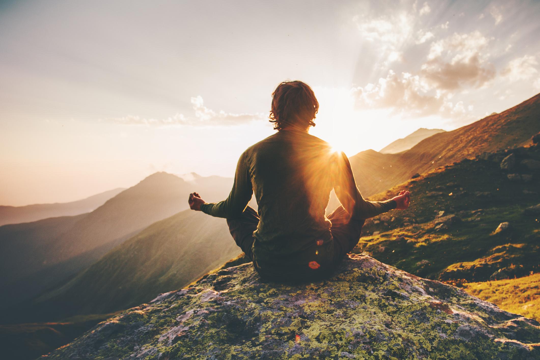 Man meditating at sunset mountains